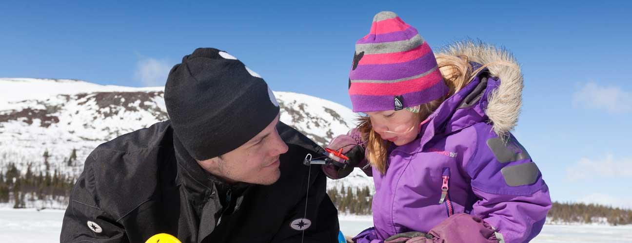 Pappa och dotter isfiskar på en fjällsjö.