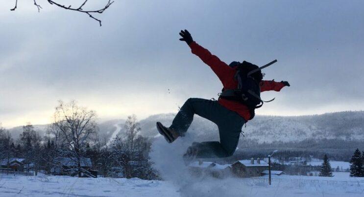 Man som hoppar i snön och gör ett hoppsasteg så att snön yr