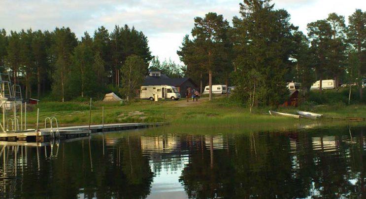 Campingplats vid spegelblankt vatten.